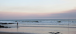 Fisherman fishing on beach during dusk, Viana do Castelo, Norte Region, Portugal