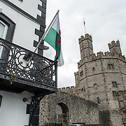 A Welsh flag flies from the patio of a building outside the castle walls at Caernarfon Castle in northwest Wales. A castle originally stood on the site dating back to the late 11th century, but in the late 13th century King Edward I commissioned a new structure that stands to this day. It has distinctive towers and is one of the best preserved of the series of castles Edward I commissioned.