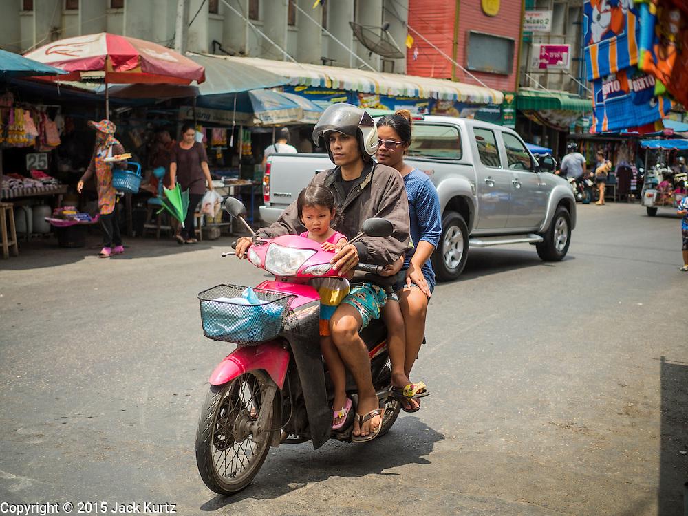 13 MAY 2015 - SAMUT SONGKRAM, SAMUT SONGKRAM, THAILAND:    A family rides a motorcycle through Samut Songkram (also called Mae Klong), Thailand.     PHOTO BY JACK KURTZ