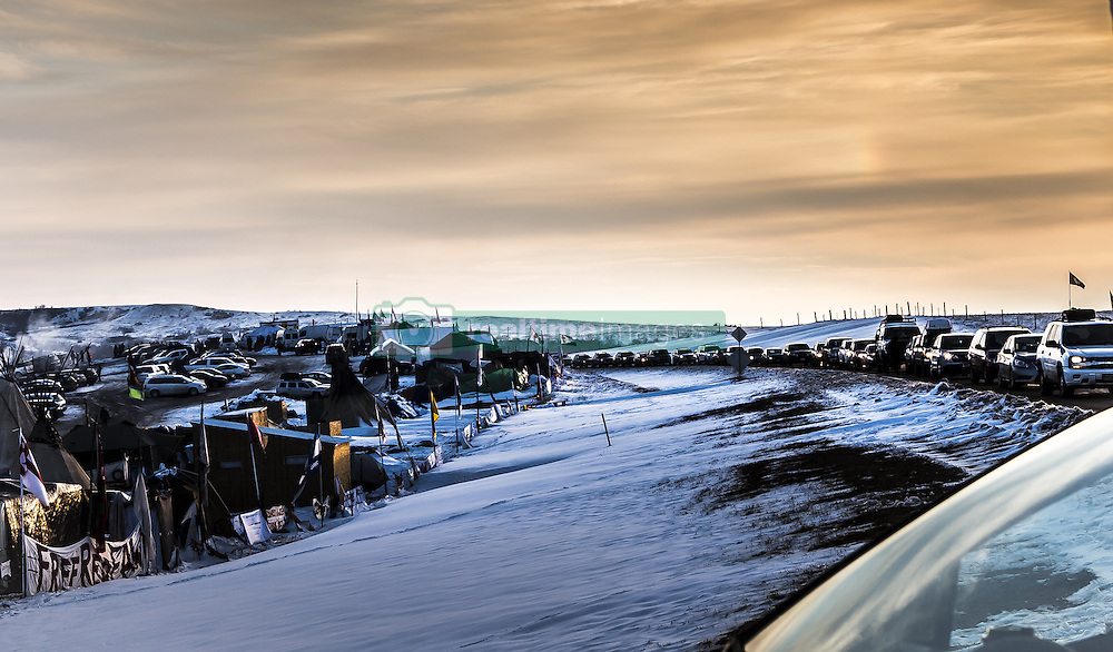 December 3, 2016 - Cannonball, North Dakota, United States - Cars lined up on highway 1806, waiting to enter the camp.  Veterans arrived en mass to Standing Rock, bringing a massive amount of supplies including winter clothing, food and firewood by the truck load.  Over 5000 veterans are anticipated to arrive by Sunday evening, prior to various actions slated to place. (Credit Image: © Michael Nigro/Pacific Press via ZUMA Wire)