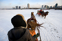 Horse drawn carriages take people across frozen Songhua river during winter in Harbin China