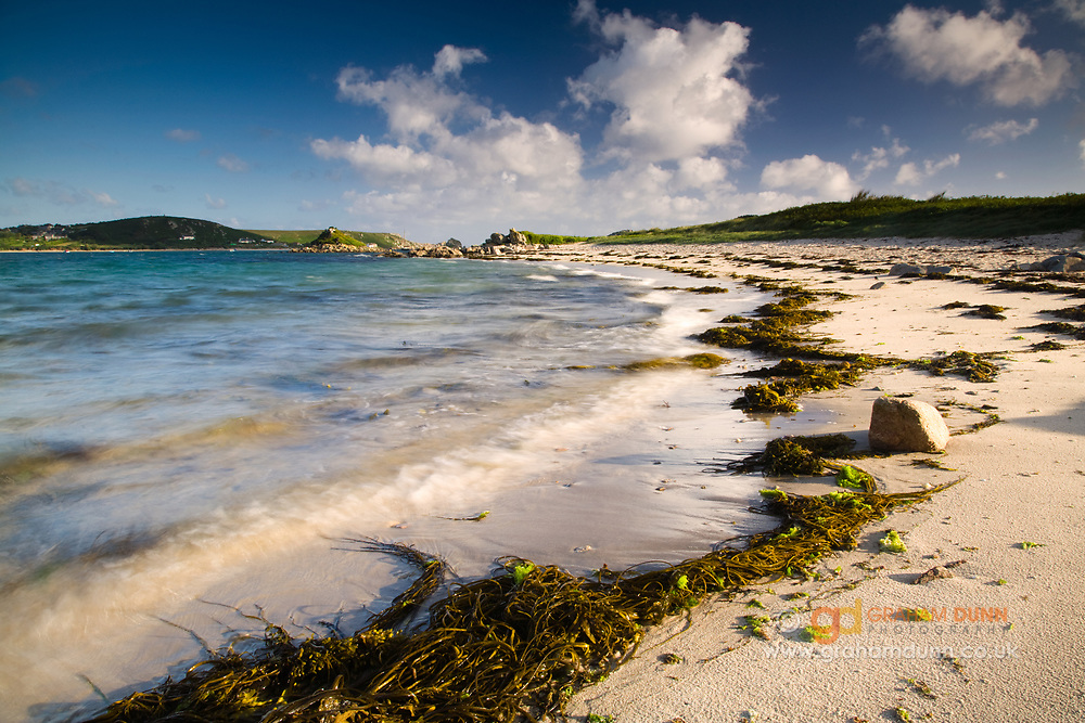 The golden sands of Tresco's Saffron Cove. Plumb Island and Bryher are seen in the distance. Isles of Scilly, Cornwall, UK