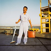 An aircraft cleaner from Kathmandu, Nepal, stands in white overalls with his bucket and mop on the tarmac at Bahrain International airport. It is another hot day in this key hub airport in this Gulf region, providing a gateway to the Northern Gulf. The airport is the major hub for Gulf Air which provides 52% of overall movements and is also the half-way point between Western Europe and Asian destinations such as Hong Kong and Beijing. Gulf states also rely on the workforces from south-Asia such as India, Pakistan, Sri Lanka and Bangladesh whose wages are often low and harsh living conditions compared to local nationals and tourists who enjoy superior accommodation. Picture from the 'Plane Pictures' project, a celebration of aviation aesthetics and flying culture, 100 years after the Wright brothers first 12 seconds/120 feet powered flight at Kitty Hawk,1903.