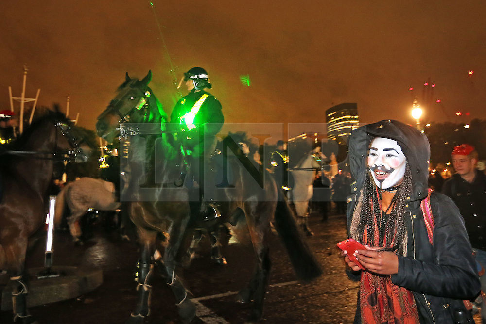 © Licensed to London News Pictures. 05/11/2015. London, UK. Mounted police have trouble controlling their mounts at Buckingham Palace as anti-capitalist protestors point a laser during the Million Mask march. Photo credit: Peter Macdiarmid/LNP