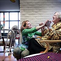 Nederland, Amsterdam , 27 oktober 2009..Mobiel platform Zona's Kiosk genaamd van de Stichting Kunst in de Zorg hier aan het werk in Sint Jacobsverzorgingstehuis..Zona's Kiosk is een reizend platform met kunst voor ouderen in zorgcentra..Op de foto zien we kunstenares Iena Stochem in innige houding dansend met een van de  ouderen van het Zorgcentrum..Mobile platform Zonas' Kiosk of the Art In Care Foundation at work in St. Jacobs home for the elderly.