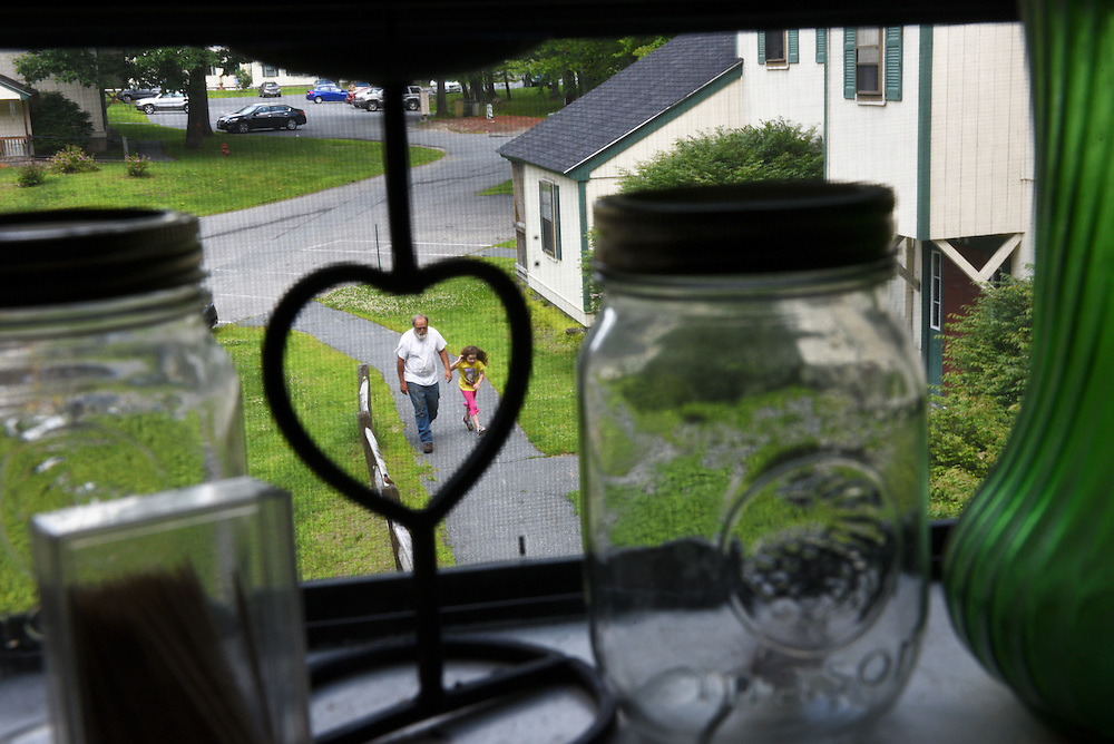 Savannah Triplett, 6, shadows her grandfather Mike Lesperance, of Bradford, left, as he makes trips from Savannah's father's Pine Tree Lane apartment to a moving van Thursday, June 25, 2015. After living with the burden of high child care costs and low wage work so that Savannah could be near her mother's family in Vermont, Mike Triplett moved the following day with his daughter to live with his family in Virginia. (Valley News - James M. Patterson)<br /> Copyright © Valley News. May not be reprinted or used online without permission. Send requests to permission@vnews.com.