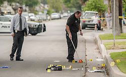 August 21, 2017 - Orange, CA, USA - An detective looks at the evidence in the street as an evidence technician takes measurements while police investigate a shooting that turned deadly in Orange, CA early Monday morning, August 21, 2017. (Credit Image: © Ken Steinhardt/The Orange County Register via ZUMA Wire)