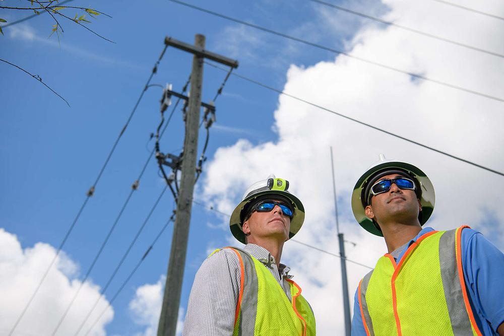 Line workers standing under power lines.
