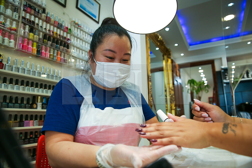 © Licensed to London News Pictures. 13/07/2020. London, UK. Nail beautician, HIEN THI THANH TRAN shows KRISTINA'S nails in her salon in North London. Nail technicians and nail salons across the UK closed on 23 March following the coronavirus lockdown. As COVID-19 lockdown restrictions are eased, nail salons reopen today. Nail technicians and their clients are required to wear face coverings. Photo credit: Dinendra Haria/LNP