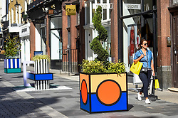 "© Licensed to London News Pictures. 14/09/2019. LONDON, UK.  The ""Walala Lounge"" opens in Mayfair's South Molton Street.  Artist and designer Camille Walala's installation comprises 10 sculptural benches, accompanied by planters and a series of oversized flags strung, bunting-style, from shopfront to shopfront, converting the street into an immersive corridor of colour as part of this year's London Design Festival.  Photo credit: Stephen Chung/LNP"