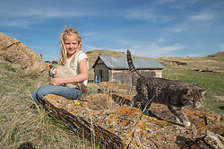 "Kennedy Koss holds her cats on the Koss's land in Eastern Montana on May 11, 2013. The Koss's work with The Nature Conservancy on the ""grass bank"" project which is an innovative way to leverage conservation gains, in which ranchers can graze their cattle at discounted rates on Conservancy land in exchange for improving conservation practices on their own ""home"" ranches. In 2002, the <br /> Conservancy began leasing parts of the ranch to neighboring ranchers who were suffering from several years of severe drought essentially offering the Matador's grass to neighboring ranches in exchange for their  participation in conservation efforts. Thirteen ranchers graze their cattle on the Matador and the grassbank has enabled TNC to leverage conservation on more than 225,000 additional acres of private land without the cost of purchase of the land or of easements. The grassbank has helped keep ranchers from ""busting sod,"" or  plowing up native grassland to farm it; helped remove obstacles to pronghorn antelope migration; improved habitat for the Greater Sage-Grouse and reduced the risk of Sage-Grouse colliding with fences; preserved prairie dog towns (thereby preserving an important food source for the endangered black-footed ferret) and prevented the spread of noxious weeds. (Photo By Ami Vitale)"