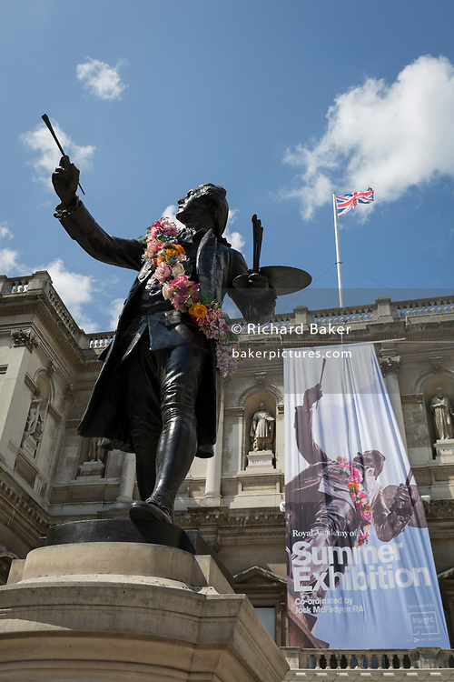 """The statue of Sir Joshua Reynolds outside the Royal Academy in Piccadilly during the Summer Exhibition, on 5th August 2019, in London, England. This is a new cast of the original that was first exhibited outside the RA in 1904 and is an allegory of the human need for new challenges, of our instinct to always be scanning the horizon and the future. Sir Joshua's statue stands in the """"Annenberg Courtyard"""" of Burlington House."""