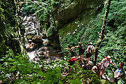 """Hikers explore verdant Zadlascica river canyon, in the Tolmin gorges (Tolminska korita), Triglav National Park, Julian Alps, Slovenia, Europe. Tolmin gorges (Tolminska korita) are among the longest and deepest gorges in Slovenia and are the lowest point (180 meters elevation) in Triglav National Park (TNP). Walk a trail to the confluence of two gorges (Tolminka and Zadlascica rivers), then along Zadlascica river canyon (locally called Skakalce, """"the jumps"""") up to a chock stone called the """"Bear's Head."""" Walk onwards to the scenic Devil's Bridge (Hudicev most, built 1907), which carries Tolmin-Cadrg road sixty meters above Tolminka River, then loop on foot back to the parking lot at the Triglavski narodni park (TNP) sign, near Zatolmin, Slovenia, Europe."""