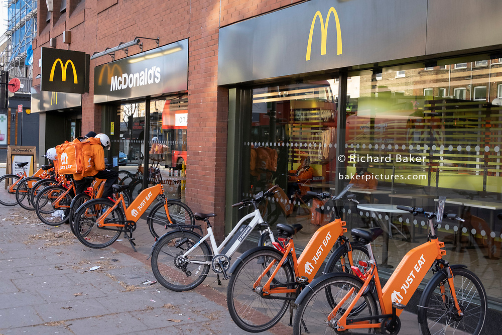As Londoners increasingly turn to takeaway deliveries supplied by the casual riders of the gig economy, eBikes are lined up outside the McDonalds on the Walworth Road, during the third lockdown of the Coronavirus pandemic, on 11th March 2021, in London, England.