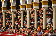 """Crowds of people watching the bullfighting. Bullfighting in Sevilla's famous bullring """"La Real Maestranza"""" is a significant part of the Feria de Abril..The Feria de abril de Sevilla, """"Seville April Fair"""" dates back to 1847. During the 1920s, the feria reached its peak and became the spectacle that it is today. It is held in the Andalusian capital of Seville in Spain. The fair generally begins two weeks after the Semana Santa, Easter Holy Week. The fair officially begins at midnight on Monday, and runs six days, ending on the following Sunday. Each day the fiesta begins with the parade of carriages and riders, at midday, carrying Seville's citizens to the bullring, La Real Maestranza...For the duration of the fair, the fairgrounds and a vast area on the far bank of the Guadalquivir River are covered in rows of casetas (individual decorated marquee tents which are temporarily built on the fairground). Some of these casetas belong to the prominent families of Seville, some to groups of friends, clubs, trade associations or political parties. From around nine at night until six or seven the following morning, at first in the streets and later only within each caseta, crowds of people party and dance Sevillanas, traditional Flamenco dances, Sevillan style drinking Jerez sherry, or Manzanilla wine, and eating tapas. .."""
