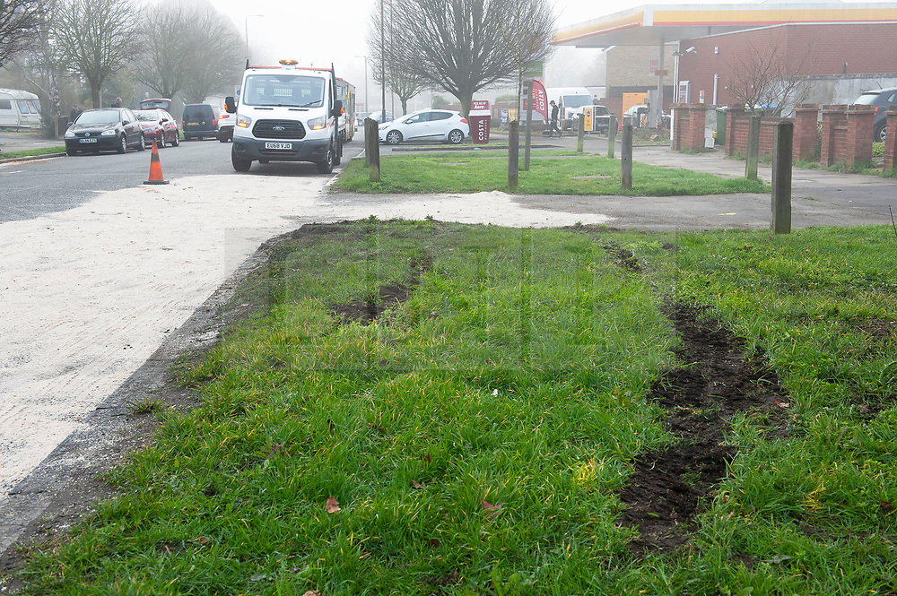 © Licensed to London News Pictures. 23/02/2019. Eltham, Tyre marks on the grass at the scene,Highways maintenance team cleaning up by putting sand over oil and petrol on the road. At approximately midnight a white van failed to stop for police in Eltham. The white van was in collision with a Citreon C3 car despite the best effort of emergency service the male and female occupants were pronounced deceased on scene. Photo credit: Grant Falvey/LNP