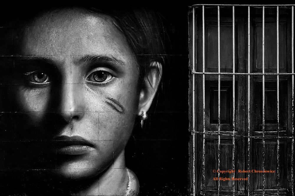 Hidden Violence (B&W):  An advertisement against domestic violence depicts a young ladies bruised face and was found next to a secured home front doorway and unfortunately mirrors the situation found in many a typical household, Trinidad Cuba.