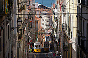 As a local leans out from a window above and others walk uphill, one of the two cars of the funicular railway climbs the steep gradient of on Rua de Bica de Duarte Belo (Elevador da Bica), on 13th July 2016, in Bairro Alto district, Lisbon, Portugal. The mechanical motor of the elevator was installed in 1890, but the lift only began functioning on 28 June 1892, after a couple of years of tests. The Bica Funicular is a funicular railway line in the civil parish of Misericórdia, in the municipality of Lisbon, Portugal. It connects the Rua de São Paulo with Calçada do Combro/Rua do Loreto, operated by Carris. (Photo by Richard Baker / In Pictures via Getty Images)