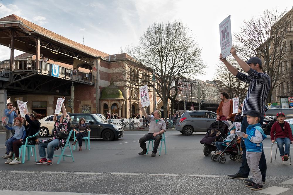 """Mehrere dutzend Aktivisten von Bizim-Kiez mobilisieren am Schlesischen Tor in Berlin Kreuzberg für die Mieterdemonstration """"Widersetzen"""" vom 14.04.2018. Während Grün-Phasen der Fußgängerampel setzen sich die Demonstranten symbolisch mit Stühlen auf die Straße und verteilen Flugblätter.<br /><br />[© Christian Mang - Veroeffentlichung nur gg. Honorar (zzgl. MwSt.), Urhebervermerk und Beleg. Nur für redaktionelle Nutzung - Publication only with licence fee payment, copyright notice and voucher copy. For editorial use only - No model release. No property release. Kontakt: mail@christianmang.com.]"""
