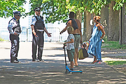 ©Licensed to London News Pictures 21/05/2020<br /> Greenwich, UK. Police officers on patrol in the park talking to a family. People out and about in Greenwich park, Greenwich, London this afternoon enjoying lockdown freedom as the mini heatwave hot weather continues with temperatures set to hit 28C in parts of the UK.  Photo credit: Grant Falvey/LNP