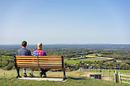 Two men sitting on a bench at the Jack and Jill Windmill location on the South Downs in East Sussex England