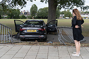 The aftermath of a crashed Audi car that has crashed through railings of Ruskin Park, a public space in Herne Hill on 21st August 2020, in London, United Kingdom. The car was seen speeding through Ferndene Road, a residential street in Lambeth, bouncing off a speed hump at great speed, colliding with a parked car and crashing through railings. The two occupants left the scene on foot and no-one was injured. Two males were later detained.