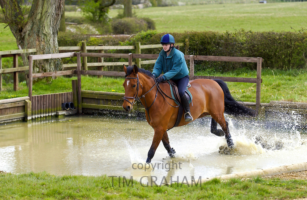 Young woman rides Cleveland Bay cross Thoroughbred horse in cross country event in the Cotswolds, Gloucestershire, UK