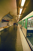 Paris metro at Mairie d'Issy station, train and passengers on the platform. Paris, France.