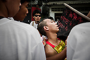 A warrior passes out during street procession near Phuket town. Every year during the ninth lunar month of the Chinese calendar, the Phuket Vegetarian Festival kicks off. The religious festival in Phuket, Thailand, lasts for 10 days, during which sacred rituals take place in the many Chinese shrines and temples. Walking on fire and climbing ladders with bladed rungs barefoot are two of several rituals believed to bring good fortune. The main purpose of the festival, however, is spiritual cleansing and merit-making.<br />A chosen few among the participants, called warriors, will pierce themselves with objects such as nails, swords, and knives. The piercing takes place in a shrine and is followed by the most spectacular part of the festival, the street processions: just like in a parade they file along the streets of Phuket, with groups of one or several pierced warriors leading a number of people behind them. Onlookers throw fireworks at them as they pass; these are intended to be as loud as possible as the common belief is that this will banish evil spirits. The warriors walk and dance in a trance-like state, unshaken by the noise.