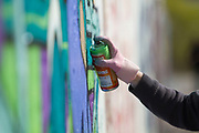 A graffiti artist holds a can of spray as he paints on the wall at Mauerpark Berlin, Germany, April 08, 2012.