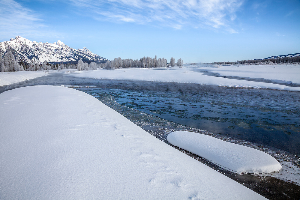 Sub zero temperatures create ice flows on the Snake River near Teton Village in Wyoming on a winter morning.  Licensing and Open Edition Prints.