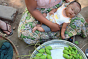 A woman with a young baby sells mangoes at Danyingone Station on 19 March 2016 in Yangon, Myanmar. At Danyingone Station, one of the Circular Railways 39 stations, the market spills out onto the tracks.