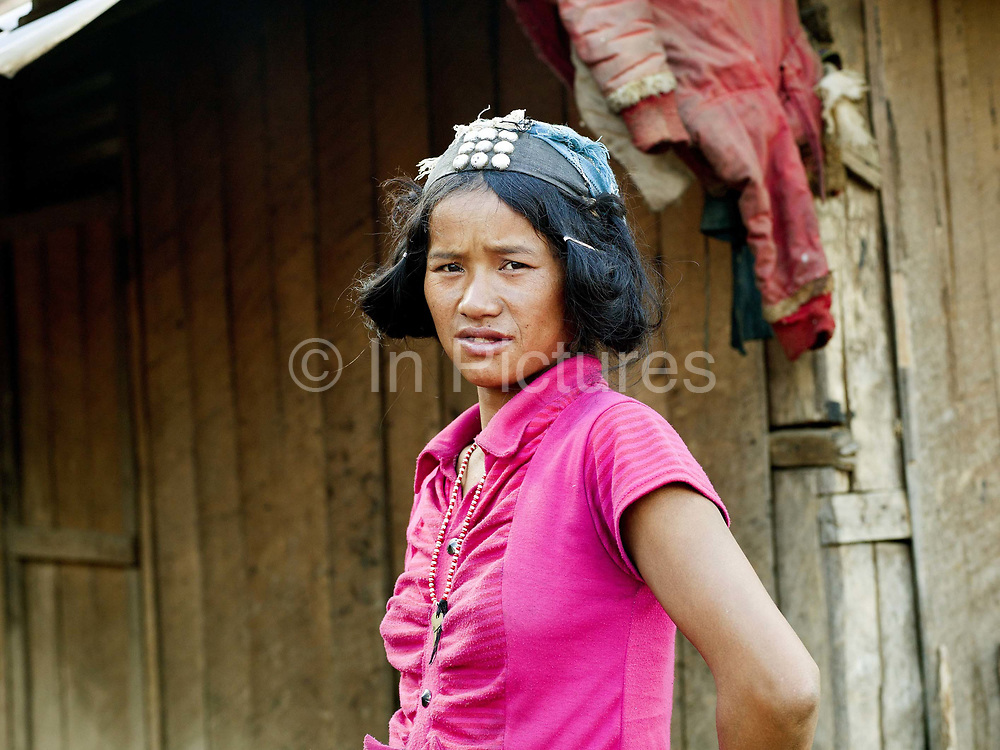 A portrait of an Akha Cherpia ethnic minority woman  wearing part of her traditional headdress and modern clothing in Ban Nam Hin, Phongsaly province, Lao PDR. One of the most ethnically diverse countries in Southeast Asia, Laos has 49 officially recognised ethnic groups although there are many more self-identified and sub groups. These groups are distinguished by their own customs, beliefs and rituals. Details down to the embroidery on a shirt, the colour of the trim and the type of skirt all help signify the wearer's ethnic and clan affiliations.