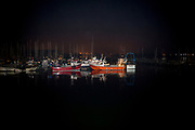 A night-time seascape of a moored fishing boat fleet in a North Sea town harbour, on 25th September 2017, in Amble, Northumberland, England.
