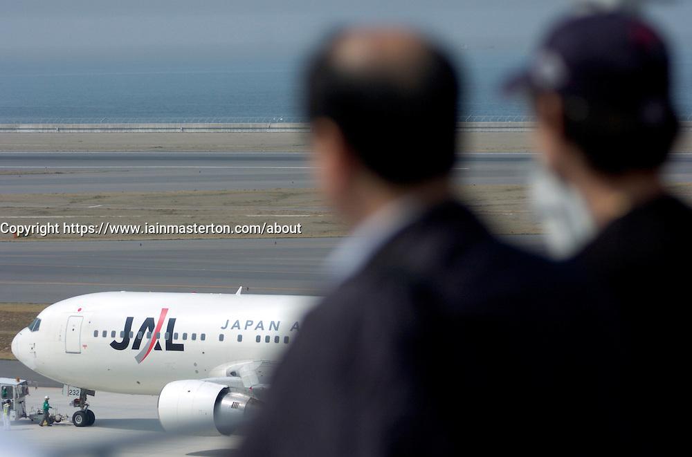 Visitors looking at airline at skydeck viewing platform at Nagoya Airport in Japan