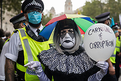 A clown joins fellow climate activists from Extinction Rebellion at a 'Carnival of Corruption' protest against the government's facilitation and funding of the fossil fuel industry on 3 September 2020 in London, United Kingdom. Extinction Rebellion activists are attending a series of September Rebellion protests around the UK to call on politicians to back the Climate and Ecological Emergency Bill (CEE Bill) which requires, among other measures, a serious plan to deal with the UK's share of emissions and to halt critical rises in global temperatures and for ordinary people to be involved in future environmental planning by means of a Citizens' Assembly.