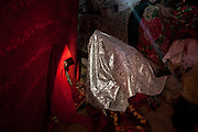 Ikhbal, 15, (white veil) recently married, is kept hidden being a large red hanging cloth, inside a yurt, where she will stay for a few days. She will sleep there with her husband, be fed etc. Later, she will move to her husband's home. At the camp of Tash Seri (Mustafa Qol's camp). ..Trekking through the high altitude plateau of the Little Pamir mountains, where the Afghan Kyrgyz community live all year, on the borders of China, Tajikistan and Pakistan.
