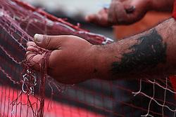 Particolare di un braccio  tatuato di un pescatore che sistema le reti.