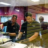 (L-R) Owner of Badlands Grill William Mataya, 44, and Aaron Baca, 26, work together to prepare the evenings meals for the dinner at Rehoboth Christian School.