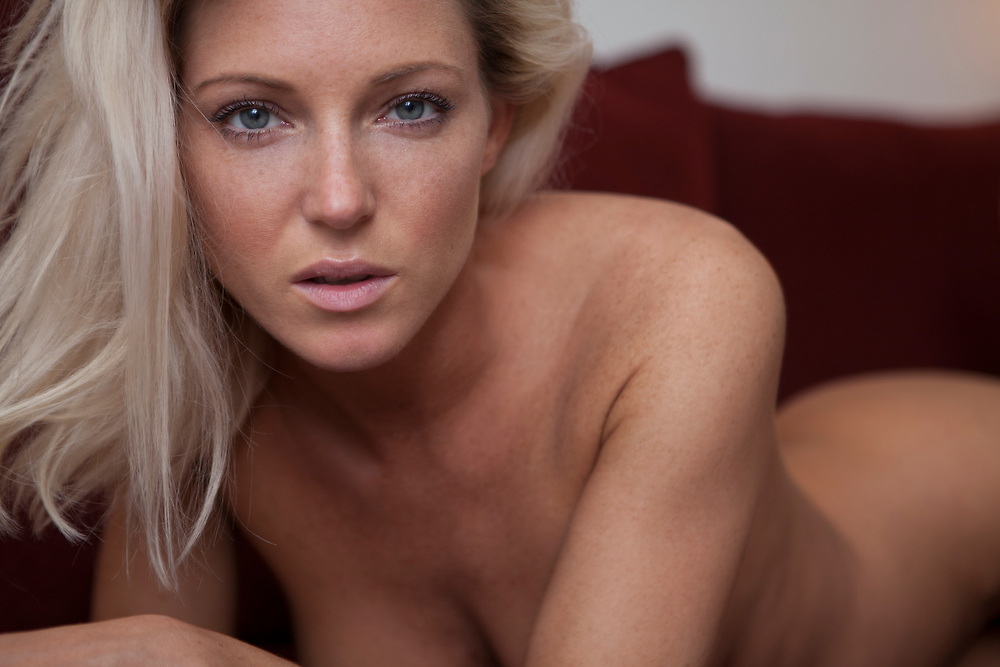 Reclining blond nude woman photographed looking at the camera