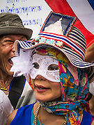 """02 JUNE 2013 - BANGKOK, THAILAND:   An anti-government protester with a picture of Bhumibol Adulyadej, the King of Thailand, in her hat, marches with an anti-government protesters. The so called White Mask protesters are strong supporters of the Thai monarchy. About 300 people wearing the Guy Fawkes mask popularized by the movie """"V for Vendetta"""" and Anonymous, the hackers' group, marched through central Bangkok Sunday demanding the resignation of Prime Minister Yingluck Shinawatra. They claim that Yingluck is acting as a puppet for her brother, former Prime Minister Thaksin Shinawatra, who was deposed by a military coup in 2006 and now lives in exile in Dubai.   PHOTO BY JACK KURTZ"""
