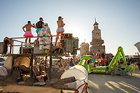 Performance at The Folly<br /> by: Dave Keane & The Folly Builders<br /> from: San Francisco, CA<br /> year: 2019<br /> <br /> The Folly represents an imaginary shantytown of funky climbable towers and old western storefronts, cobbled together from salvaged and reclaimed lumber from original San Francisco Victorians to be reborn in the desert, affording shelter, entertainment and perspective to the community.<br /> <br /> URL: www.thefollybrc.com<br /> Contact: info@thefollybrc.com<br /> <br /> https://burningman.org/event/brc/2019-art-installations/?yyyy=&artType=H#a2I0V000001AVkAUAW
