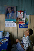 A man looks at a portrait of the king Bhumibol Adulyadej while he has lunch, in Bangkok, Thailand. PHOTO TIAGO MIRANDA