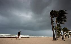 A man walks along the beach with heavy winds and threatening skies in anticipation for Hurricane Irma, in Hollywood, Fla., Saturday, September 9, 2017. THE CANADIAN PRESS/Paul Chiasson