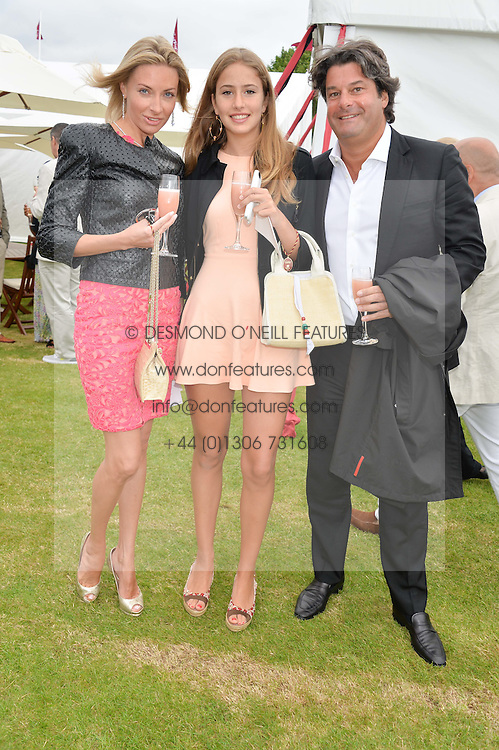 Left to right, IRINA MOROZOVA, NATASHA MOUFARRIGE and her father TIM MOUFARRIGE at the Cartier Queen's Cup Final polo held at Guards Polo Club, Smith's Lawn, Windsor Great Park, Egham, Surrey on 15th June 2014.
