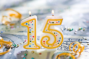 Fifteen (15) year  celebration candle on U.S. currency.