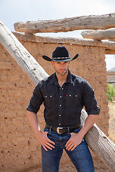 hot rugged cowboy by an adobe structure on a ranch