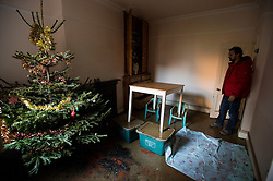 © Licensed to London News Pictures. 29/12/2015. York, UK. A tenant on Huntingdon Road in central York looks at his christmas tree and dining table propped up on boxes to protect it from flood water while he inspects damage to his home. Further rainfall is expected over coming days as Storm Frank approaches the east coast of the country. Photo credit: Ben Cawthra/LNP