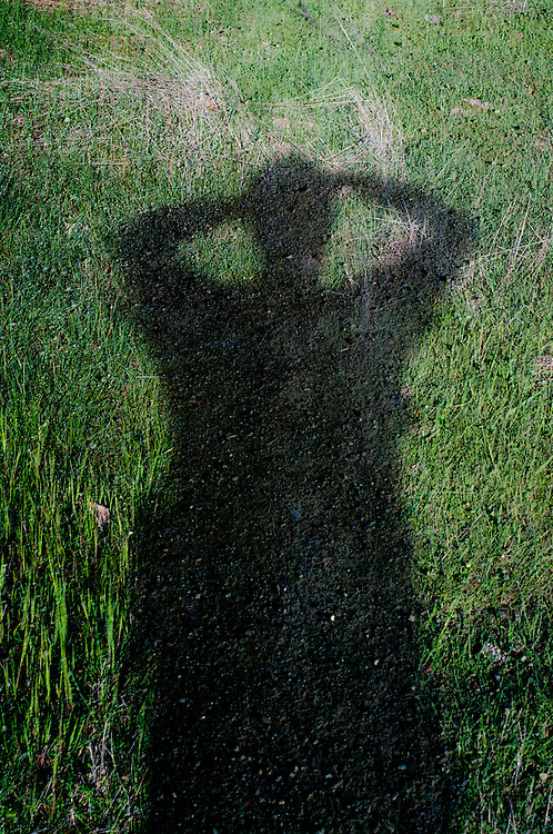 A multiple exposure photo of a man's shadow of gravel on grass.