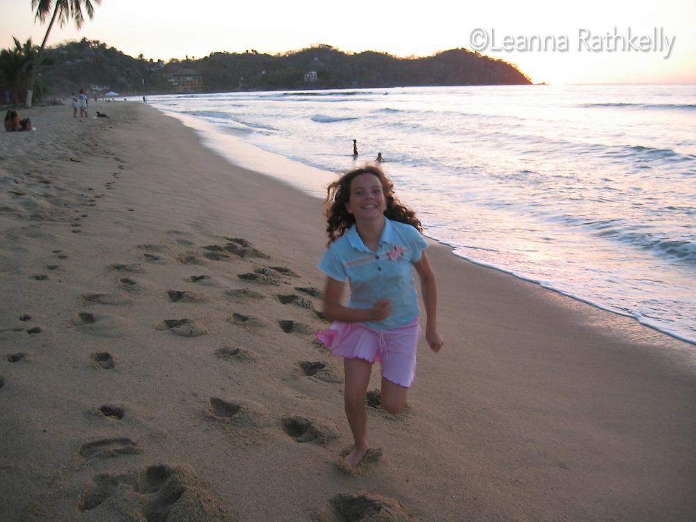A girl, 12, runs along the beach at sunset in Sayulita, Mexico